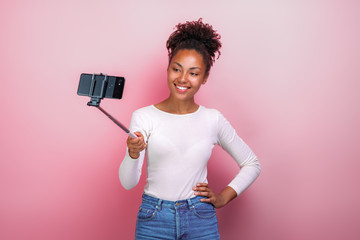 Young girl holding mobile phone takes a picture selfie - Image