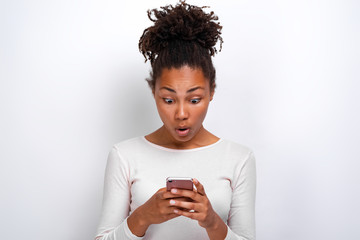 Amazed woman holding a smartphone in her hands and shocked looking at the screen- Image