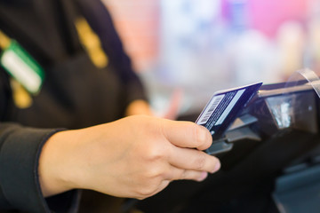 Selective focus to the cashier is swiping the credit card or member card at the card reader with the cash register machine in the store. Saleswoman receiving payment from customer in store.