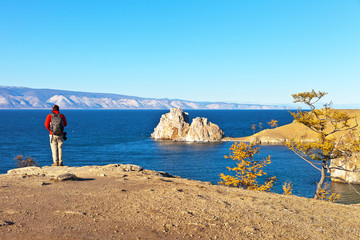 Lake Baikal and Olkhon Island on an autumn sunny day. View of the famous natural landmark - the Shaman Rock. A tourist with a backpack and a camera is standing on the shore of the Strait Small Sea