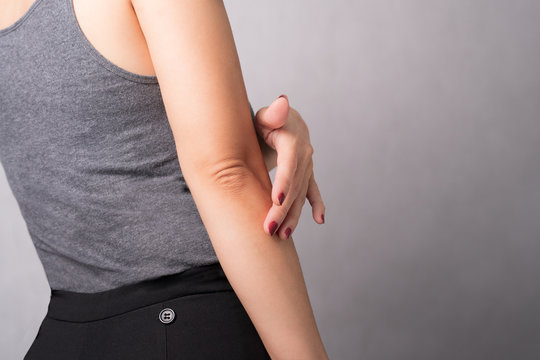 Closeup of a beautiful woman applying daily skin care lotion, moisturizer cream, on her elbow. Rough and dry skin, Lack elasticity, Aging skin problem, Dermatology, Anti-aging, Body skincare concept.