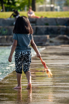 Mexican American toddler girl walking barefoot with a doll in her hand at lakefront waterfront pier. No face.