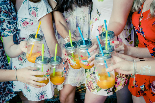 Des mains de filles qui trainquent avec un cocktail à la main
