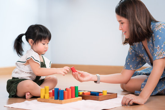 A precious moment of adorable little asian preschool girl 2 years old, learn by play wooden colorful blocks with her beautiful mother. Early education, Montessori at home, Child development concept.
