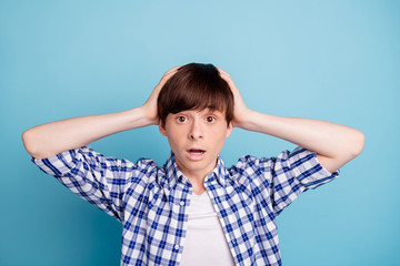 Portrait of impressed horrified boy touching his head with hands wearing checked shirt isolated over blue background
