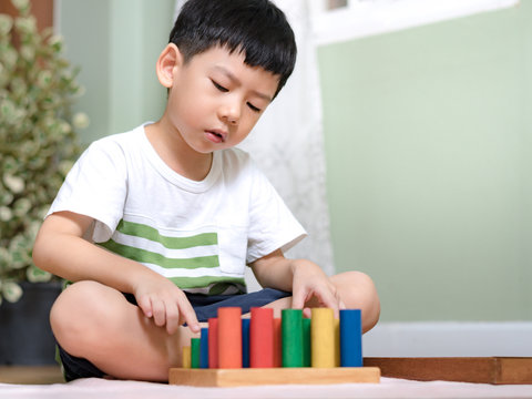 Portrair of an asian little Montessori kid (3-6) learning about size, orders, sorting, arranging by engaged colorful wooden sensorial blocks. Educational toys, Cognitive skills, Montessori activity.