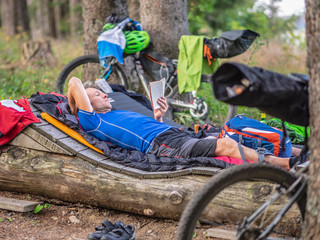 Mountain biker resting on a log reading book amidst woods, Baden-Württemberg, Germany