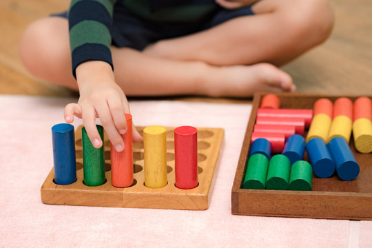 A little Montessori kid (3-6) learning about size, orders, sorting, arranging by engaged colorful wooden blocks. Educational toys, Cognitive skills, Sensorial activity, Children development concept.