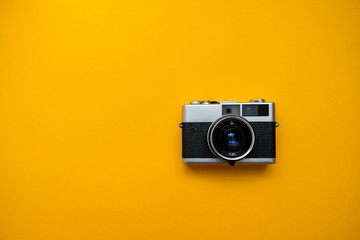 Retro Film Camera on yellow background. Photo shooting. Pop Art. Hipster Trendy Vintage Accessories. Minimal flat lay