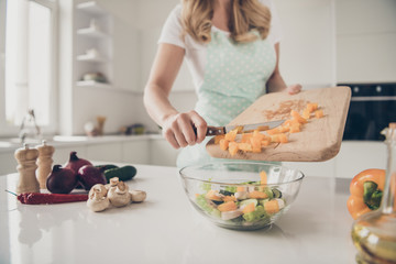 Cropped view of wavy-haired lady putting in bowl slices pieces making tasty yummy delicious dinner lunch meal in light white interior kitchen indoors
