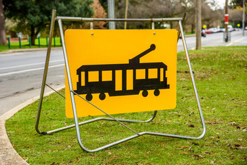 A yellow 'Tramcar' sign hanging from a metal stand, placed on the grass next to some street tram tracks.