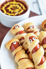 Fun food for kids. Mummy hot dogs lying on a rustic table with a bowl of ketchup and mustard dip, with spider web design. Top view, overhead position.