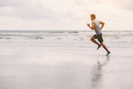 Runners. Young people running on beach. Athletic attractive people jogging on beach enjoying the sun exercising their healthy lifestyle.