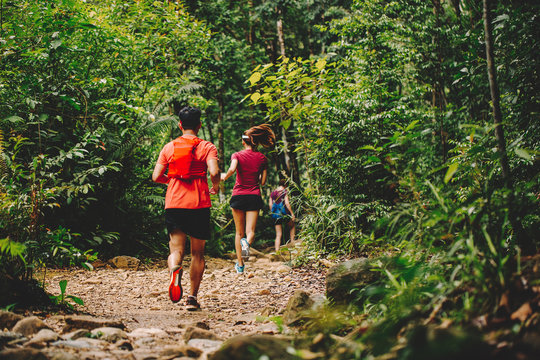 Runners. Young people  trail running on a mountain path. Adventure trail running on a mountain. Athletic attractive people running enjoying the sun exercising their healthy lifestyle.