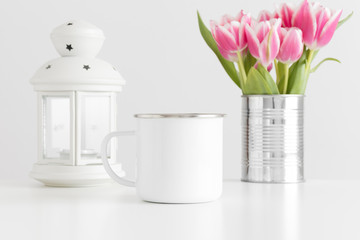 Enamel mug mockup with pink tulips in a pot and candle holder on a white table.