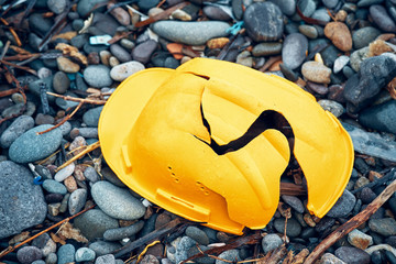 Obraz Cracked work helmet on the floor covered with pebble stones. Concept of work accident. - fototapety do salonu