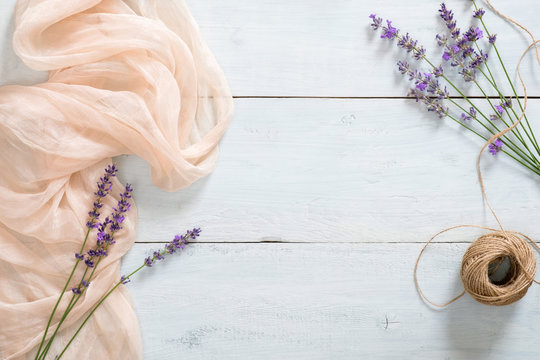 Lavender flower, pastel pink blanket and twine on rustic blue wooden background. Flat lay, top view, copy space. Banner mockup for beauty blog, summer fashion concept.