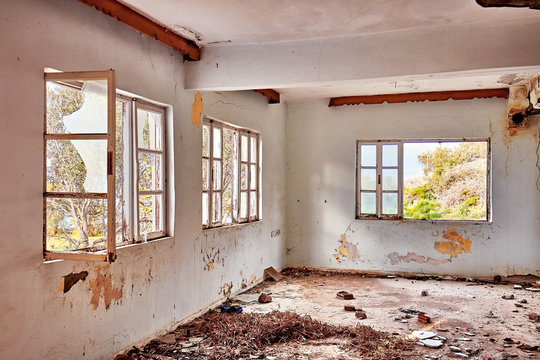 Interior of an old abandoned ruin house with white cracked walls and broken window frames