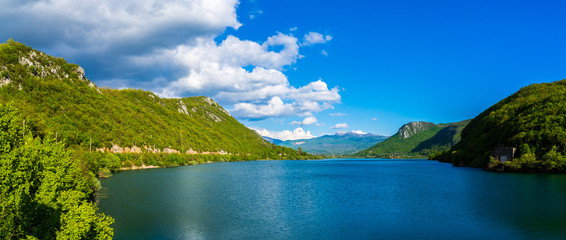 Montenegro, XXL panorama of beautiful barrier lake waters called jezero liverovoci inside green valley near niksic city surrounded by green trees and forest covering mountains and hills under blue sky Wall mural