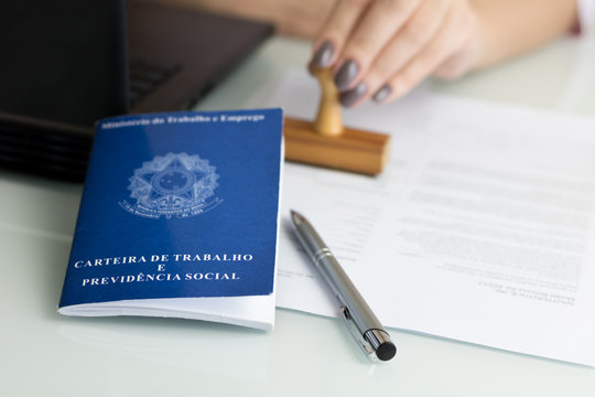 """A portfolio of Brazilian workers (Translation """"Work Permit, Ministry of Labor and Social Security Brazil CTPS""""), female hand signing a work contract background."""
