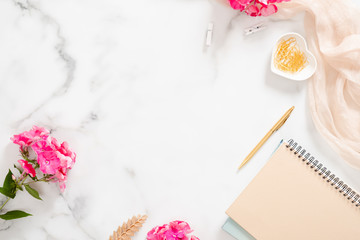 Flatlay home office desk table. Workspace with pale pastel beige notebook, pink flowers and decorations on white background. Flat lay, top view.