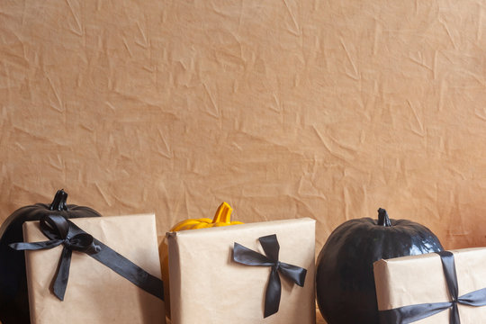 Celebrating Halloween. Orange and black pumpkins with decorated gift boxes