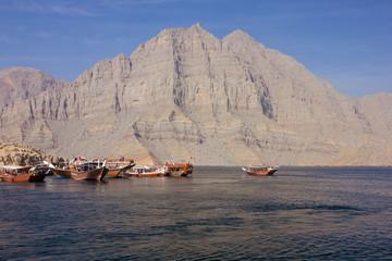 Oman fjords mountain sea view, tourist dhow boats, Khasab, Musandam peninsula