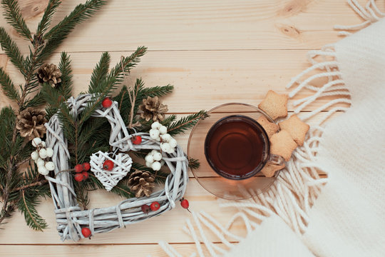 Cup of tea with cookies asterisks with a Christmas wreath heart of winter berries and a white blanket
