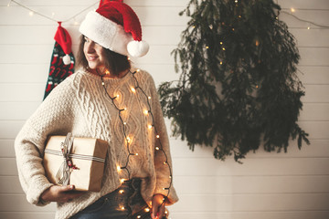 Stylish happy girl in santa hat holding christmas gift box on background of modern christmas tree, lights and stockings. Young hipster woman in cozy sweater holding present and smiling