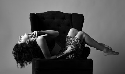 Black and white. Sensual woman in fashion underwear and leopard print skirt is sexual posing in luxury plush armchair