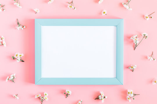 Beautiful flowers composition. Blank frame for text, flowers pattern on pastel pink background. Flat lay, top view, copy space