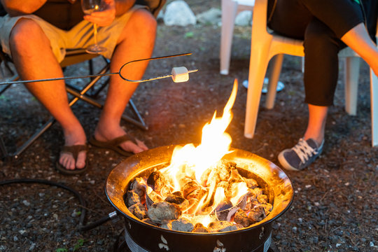 A Family around a camp fire roasting marshmallows