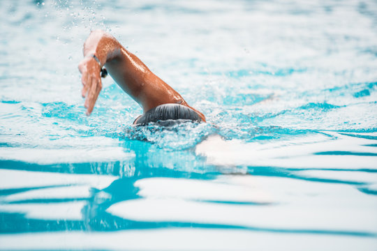 Athletic Young man swimming the front crawl in a pool. Swimming competition.