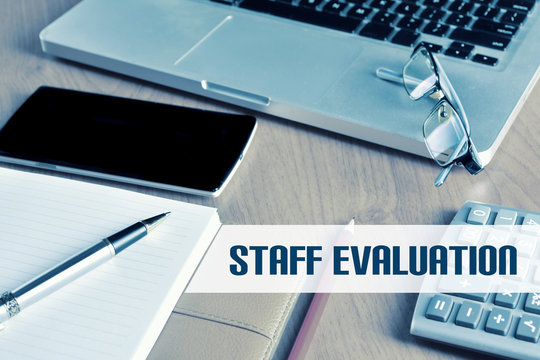 Notebook with calculator, keyboard and pen on table with text STAFF EVALUATION