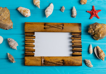 Wooden picture photo frame on blue wooden background with different sea shells