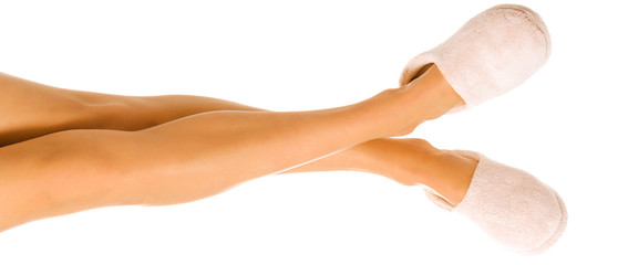 Beautiful long female legs in a comfortable slippers on the white background.