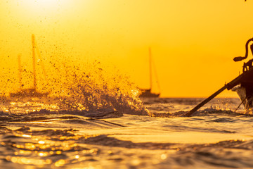 Long tail boat at sunset in the sea.