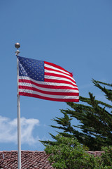 Close view of the US flag flying high over the roofs of a small coastal town under bright blue sky
