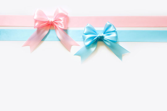 Blue and pink wide satin ribbon with a bow. White background. Birth of a boy or girl.