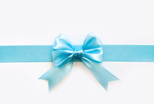 Blue wide satin ribbon with a bow. White background.