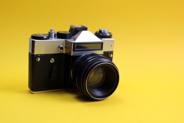 Retro camera. Old film camera on a yellow background