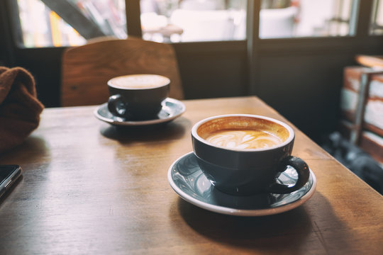 Closeup image of two blue cups of hot latte coffee on wooden table in cafe