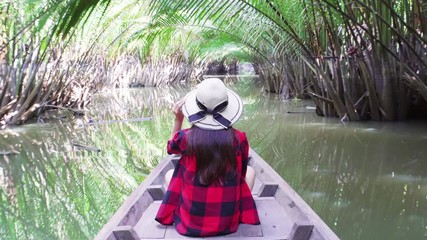 Wall Mural - Asian women sitting on a boat at tunnel from nypa fruticans or palm tree in Surat thani,Thailand.