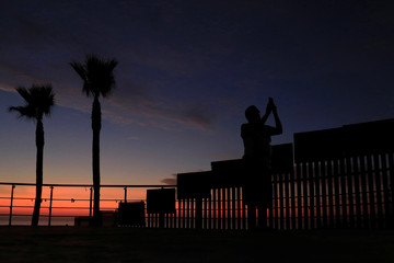 A man takes pictures with a cellphone during sunset near the border fence between Mexico and U.S. in Tijuana
