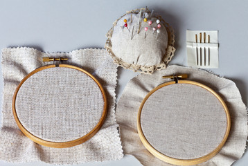 Accessories for hand embroidery: wooden hoop with canvas of different density, embroidery needles, pins and a pad for needles on the desktop. Top view, close up