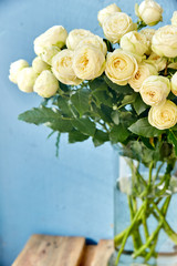 A bouquet of white roses flowers on a blue wall in a vase