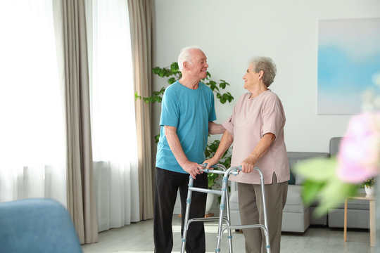 Elderly man and his wife with walking frame indoors. Space for text