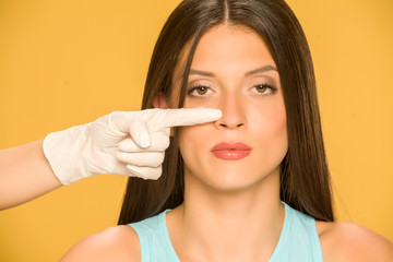 Doctor's hands touching the nose of a young woman on yellow background