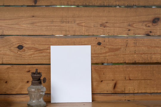 Woman holding paper blank of drawing paper paper with wooden background.