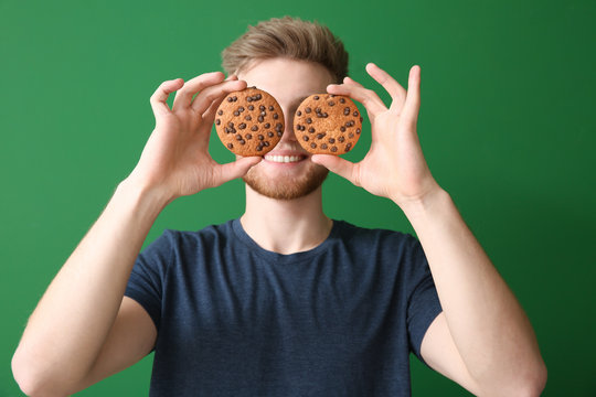 Happy young man with tasty cookies on color background